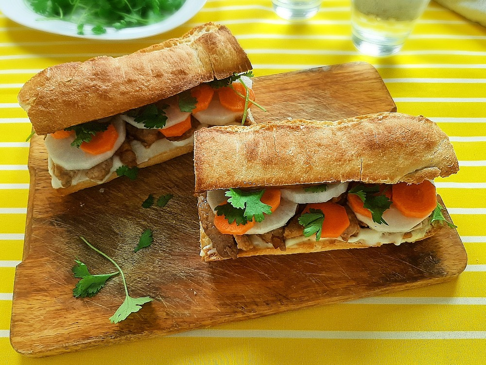 Banh Mi mit mariniertem Schweinefleisch getoppt mit Hoisinsauce und Koriander
